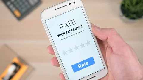 Giving a 5 (five) stars rating on a ''Rate my experience'' app on a smartphone. The consumer is satisfied with the service.
