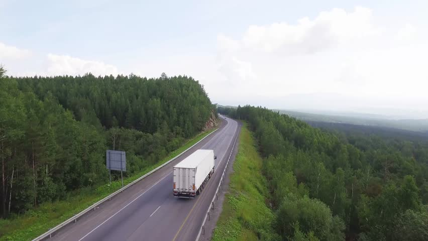 One white truck driving along the freeway amidst a dense forest in the mountains. Summer, sunny, beautiful sky with clouds. Aerial drone view.