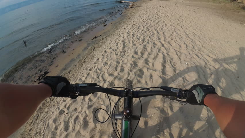 Fat bike also called fatbike or fat-tire bike in summer riding. Driving on different surfaces of stones, sand, grass, mud. A view from the first person to the steering wheel, hands and road. | Shutterstock HD Video #1007622004