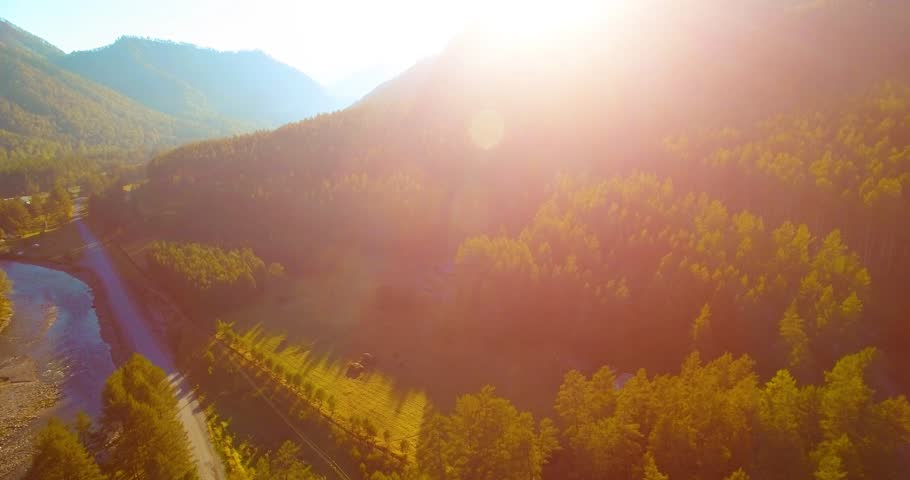 Mid-air flight over fresh mountain river and meadow at sunny summer morning. Green trees and sun rays on horizon. Rural dirt road below. | Shutterstock HD Video #1007638054