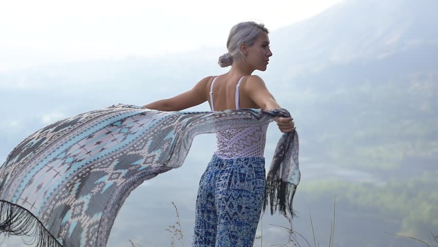 Slow motion shot of young woman holding scarf to the breeze on mountain top | Shutterstock HD Video #1007639935