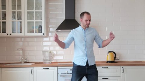 man dancing and singing in the kitchen