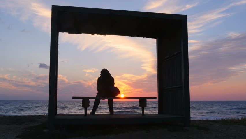 Sunset in the sea, the silhouette of the girl sits on a bench, loneliness is secluded.