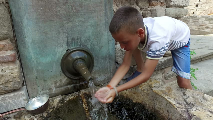 boy drinking water from hands from ancient oriental tap in the old city of Nesebar, Bulgaria
