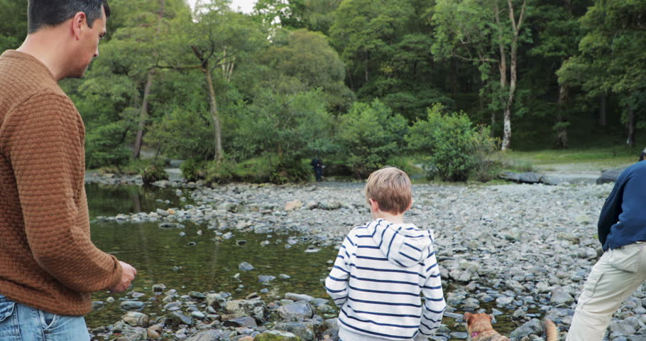 Little boy is skimming stones on a lake with his father and grandad. His dad's stone gets further than his so they start to play fight.