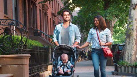 Happy couple walking in the street with baby in a stroller