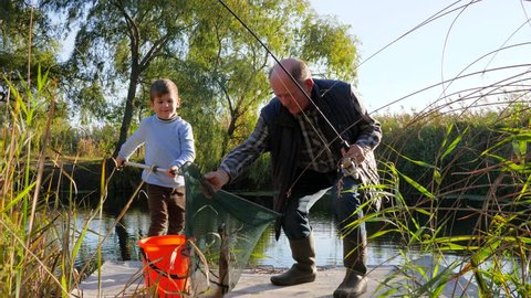 fun holidays, old fisherman and grandchildren caught crucian in lake in good weather among bulrush and trees