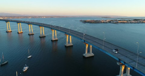 Aerial Drone video flying over the Coronado Bridge with a view of the San Diego Bay During Sunset.