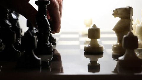 Chess being played with black pieces. Pawn being advance forward on a chess board.