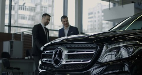 ZAPOROZHYE, UKRAINE, JANUARY 18, 2018: Elegant salesman presenting new Mercedes Benz car to potential buyer in showroom