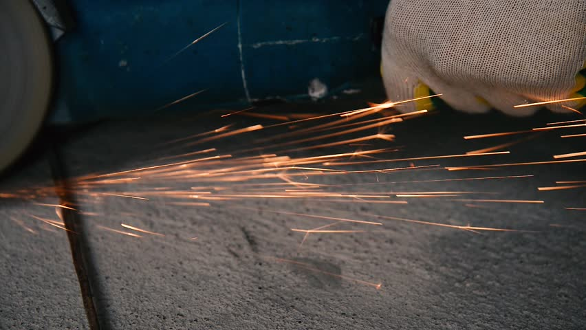 Shiny sparks from grinding metal by a grinding machine loop on a gray beton background. Slow motion at 4K resolution.