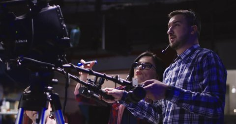 Female stage manager and cameraman working in team with professional filmmaking equipment in studio and shooting coverage.