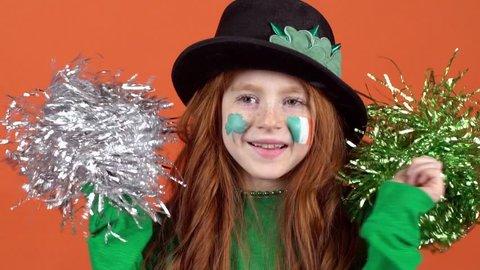 Girl red hair celebrating saint patrick's day orange background holding pom poms close-up