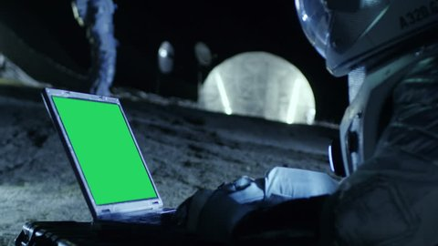 Astronaut on the Alien Planet Works on a Mock-up Green Screen Laptop. In the Background Her Crew Member and Space Habitat. Extraterrestrial Colonization Concept. Shot on RED EPIC-W 8K Helium  Camera.