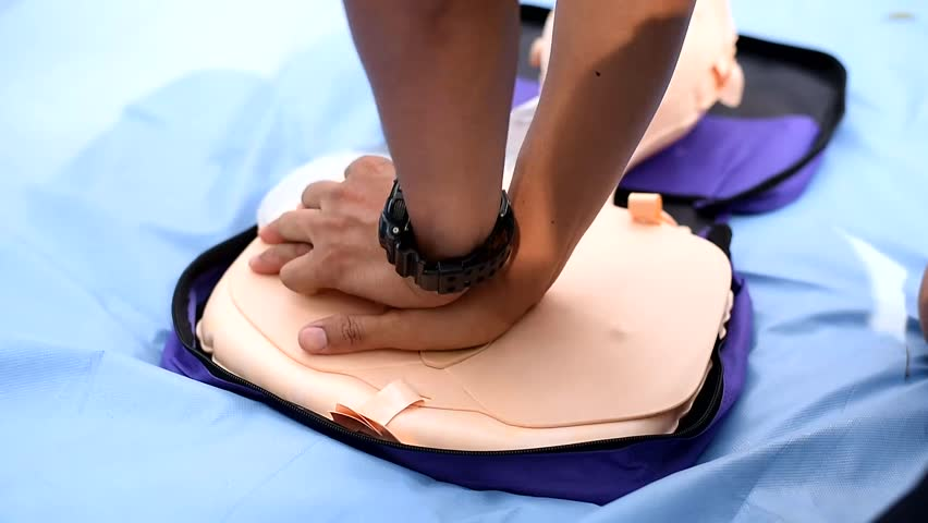 First Aid Concept - CPR Training Chest Compression on CPR Training Manikin - Dummy Situation Footage