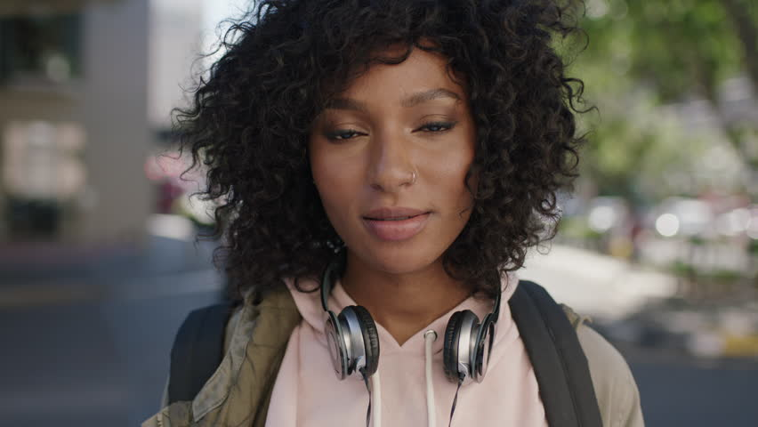 portrait of young attractive african american woman afro hairstyle smiling cheerful in city street wearing headphones urban lifestyle #1007762074