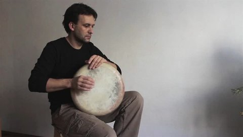Man musician plays ethnic drum darbuka close up indoors. Male hands tapping djembe bongo hands movement rhythm. Musical instruments handmade world culture sound