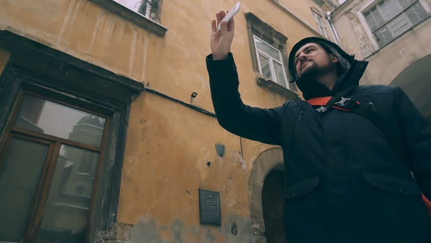 Tourist man with interest looks at the architectural buildings of the old city and shooting video on smartphone. | Shutterstock HD Video #1007794954