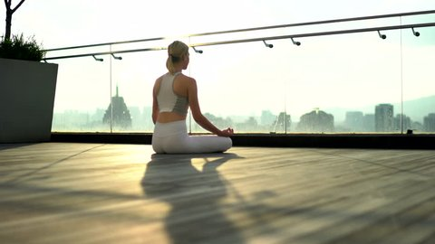 Young female in white tracksuit hands up during yoga training feeling relaxation in morning time, back view of woman meditating during yoga practice on rooftop on penthouse, scenery cityscape view
