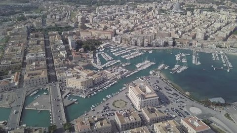 D-log aerial footage by drone, flying over the marina of Island of Ortigia, Syracuse in Sicily, Italy. Yachts in harbor - Native Video File