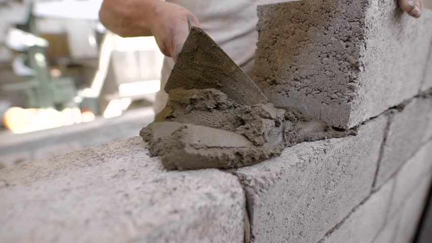 builder is imposing building solution on a wall from blocks during doing brick masonry in a construction area