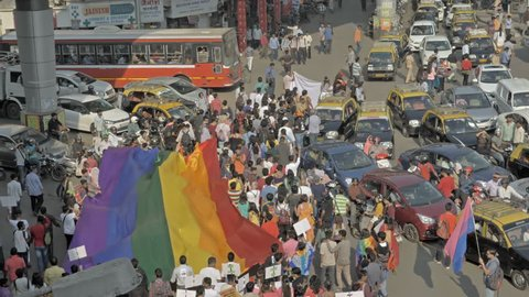 Crowd of people carrying large LGBT pride flag or rainbow flag walking through traffic jammed road during LGBT or Gay pride parade, Mumbai India (2018)