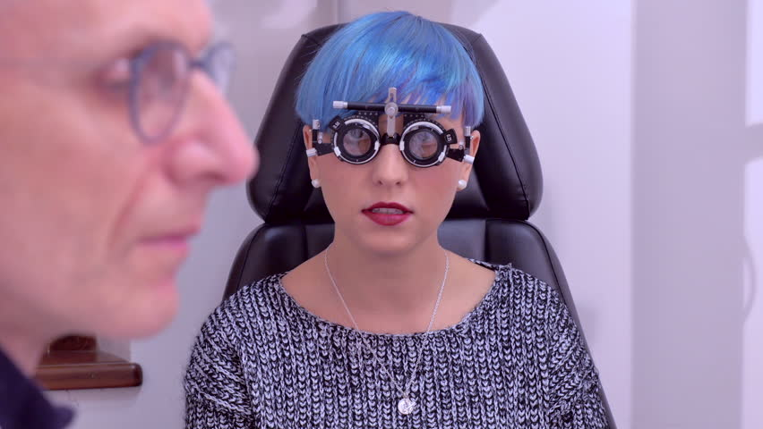 Young woman with blue hair having her eyes examined by an ophthalmologist #1007829754