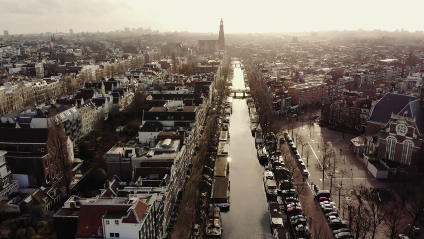 AMSTERDAM, NETHERLANDS February 18, 2018: The canals around Prinsengracht in Amsterdam at sunset. The camera flies in a slow movement over the golden water leaves the Noorderkerk on the right side and