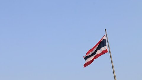 Thai national flag in blue white and red color on the flagstaff blowing with the wind on blue sky background. National flag of Thailand, three color on the fabric.