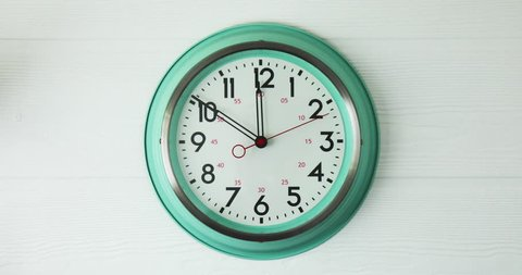 timelapse footage of a vintage green clock against a white faded background whilst time ticks on