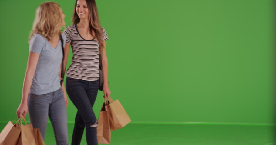 Two attractive girlfriends window shopping on greenscreen. Couple of pretty women carrying shopping bags in front green screen wall. 4k