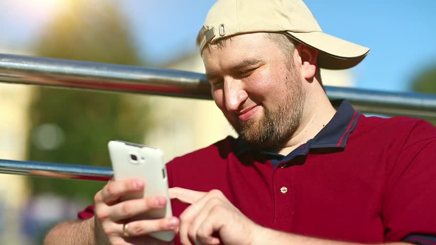 Man in baseball cap uses smartphone close-up. Fat man with white cell phone in hand | Shutterstock HD Video #1007873494