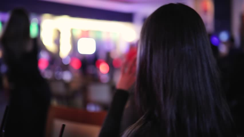 Girl taking photo while woman dancing in a night club, rear view