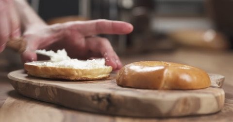 Man hands making bagel sandwich with prosciutto and cream cheese on wood board