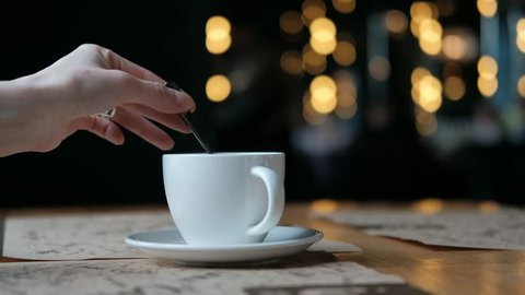 Hand of a Woman mixing coffee with a spoon. Cup of tea on the table with blurred lights on background.