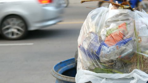 A full clogged trash can with plastic bags leftovers of food and other waste on a busy street on which cars and motorcycles drive
