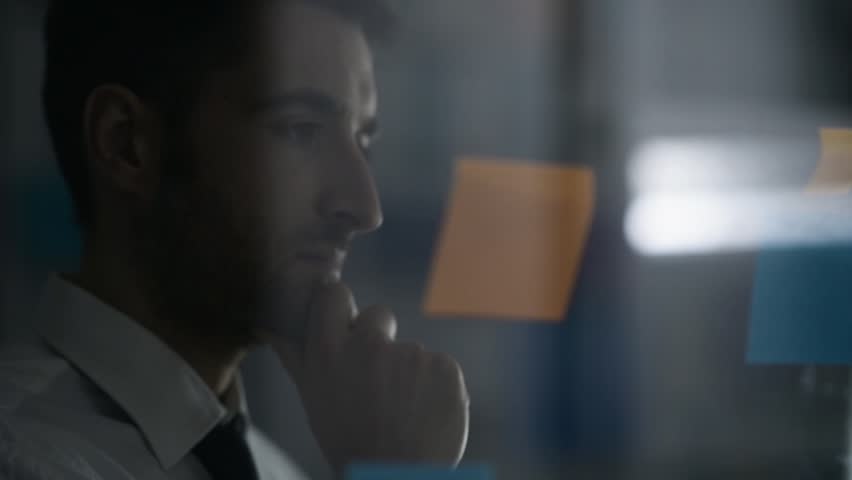 Creative smart businessman examining sticky notes in the office and thinking about innovative business strategies | Shutterstock HD Video #1007901694
