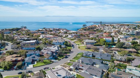 Aerial time lapse in motion or hyperlapse over Corona Del Mar in Newport Beach on sunny day blue sky day with luxury homes below.