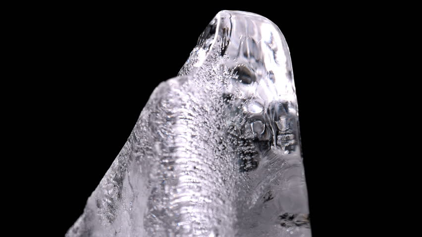 A piece of ice with bubbles slowly rotating, close up | Shutterstock HD Video #1007906254