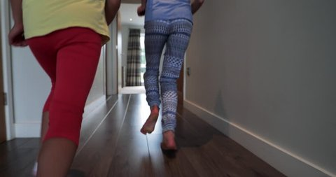 Tracking shot of two little girls playing, running in the house and jumping onto the bed.