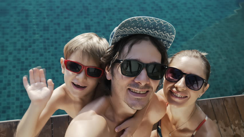 Smiling family of three in sunglasses taking selfie near swimming pool on the roof of skyscraper, waving hands, video chatting on smart phone on city background. Happy summer vacation. Travel concept.