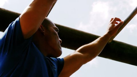 Man crossing the monkey bars during obstacle course in boot camp