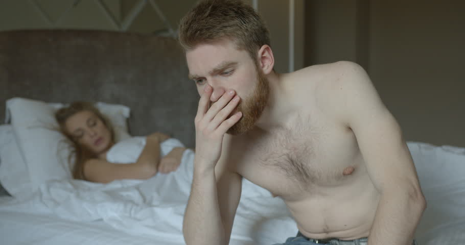 Couple is having problems in bed. The ginger head man is depressed while his disappointed angry woman in thong is leaving the room. #1007955124