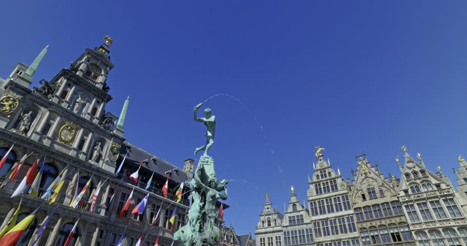 Tourists visiting Bravo statue in Grat Market square in the center of Antwerp, Belgium on a sunny day. City Hall in the background. Cinematic camera movement.
