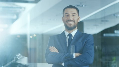 Successful Businessman Standing in the Office Smiles and Crosses Arms. Shot on RED EPIC-W 8K Helium Cinema Camera..