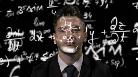 Young thoughtful attractive mathematician dressed in suit studying algebra formulas in cyber space