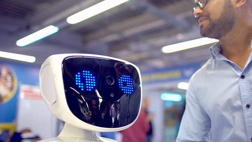 Visitors talking with humanoid robot. slow-motion. A robot with a display shows emotions, talking, confesses in love. Robot fell in love, the emotions. artificial intelligence, virtual love, vr