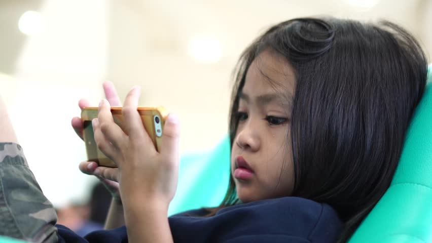 Little girl using mobile phone for looking media and playing games , video for education and family concept   Shutterstock HD Video #1008027844