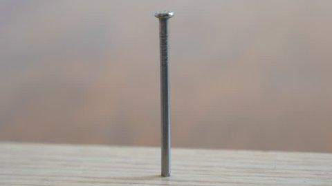 Hammering a nail on wood macro shot