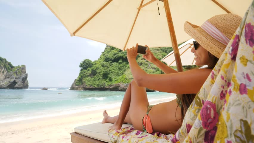 Mixed Race Young Tourist Woman Taking Smartphone Selfie Picture Relaxing on Lounge Bed near Sea on Tropical Island. Girl Using Mobile Phone at the Beach. 4K, Slowmotion. Nusa Penida, Indonesia. | Shutterstock HD Video #1008061024